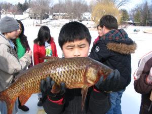 Student holding carp on frozen lake
